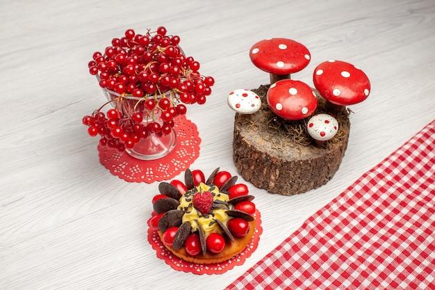Vista superior de groselha em um copo de cristal e bolo de frutas vermelhas no guardanapo de renda oval vermelha e cogumelos no toco feito à mão na mesa de madeira branca