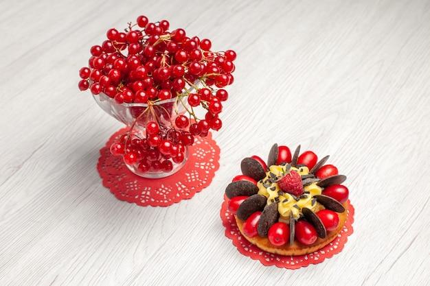 Vista superior de groselha em um copo de cristal e bolo de frutas vermelhas no guardanapo de renda oval vermelha na mesa de madeira branca