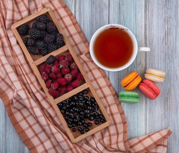 Vista superior de groselha preta com framboesas e amoras em um suporte com uma xícara de chá e macarons coloridos em uma superfície cinza