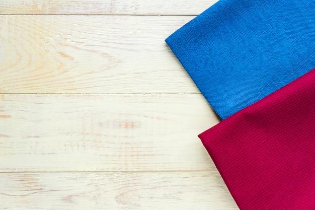 Vista superior de guardanapos de pano de cores azuis e bordô em branco rústico.