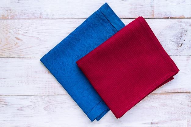 Vista superior de guardanapos de pano de cores azuis e bordô em fundo branco rústico.