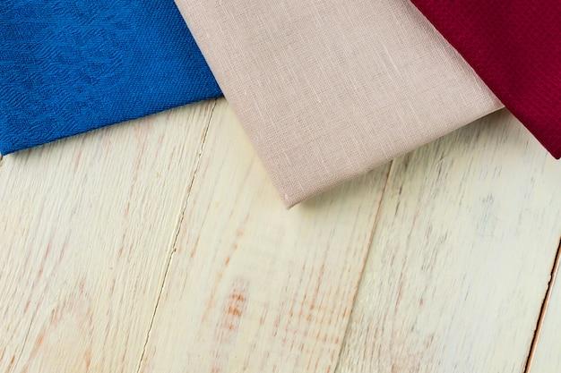 Vista superior de guardanapos de pano de cores bege, azuis e bordô em branco rústico