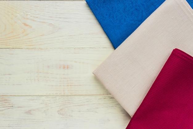 Vista superior de guardanapos de pano de cores bege, azuis e bordô sobre fundo branco rústico.