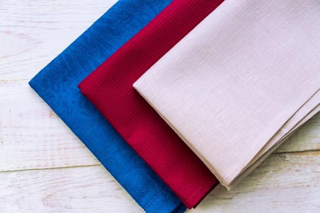 Vista superior de guardanapos de pano de cores bege, azuis e bordô sobre fundo rústico de madeira branco.