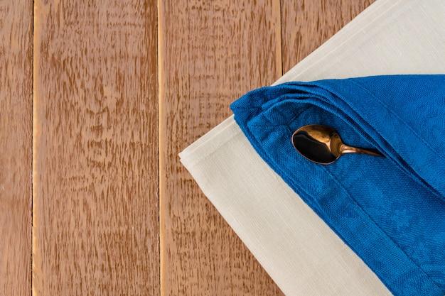 Vista superior de guardanapos de pano de cores bege, azuis e colher de chá servido na mesa de madeira.