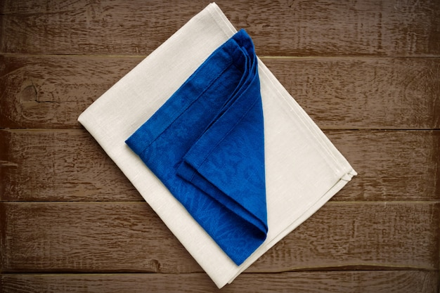 Vista superior de guardanapos de pano de cores bege e azuis sobre fundo de madeira rústico.