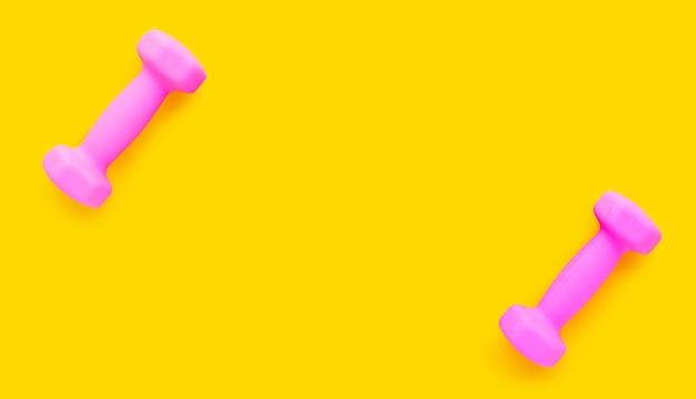 Vista superior de halteres rosa sobre fundo amarelo. copie o espaço
