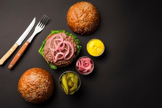 Vista superior de hambúrguer de carne com molhos e talheres