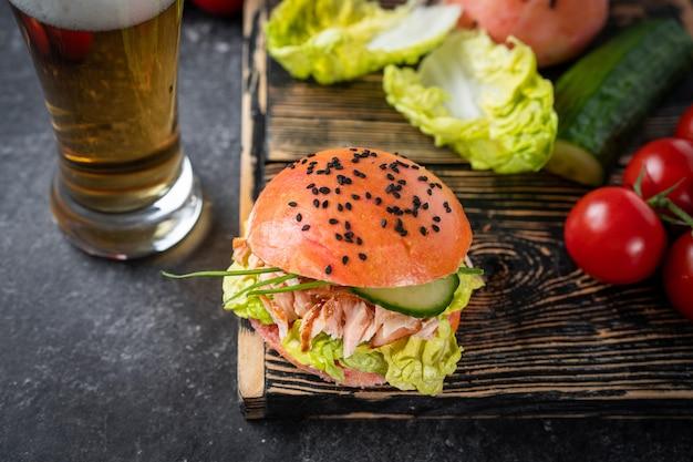 Vista superior de hambúrguer de peixe com pão rosa e samon com copo de cerveja no fundo preto