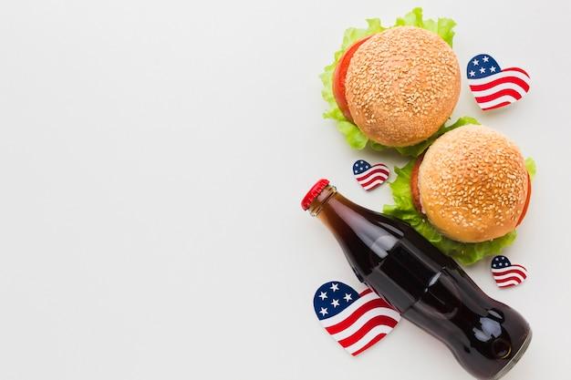 Vista superior de hambúrgueres com bandeiras e garrafa de refrigerante