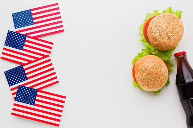 Vista superior de hambúrgueres com garrafa de refrigerante e bandeiras americanas