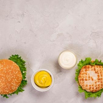 Vista superior de hambúrgueres com molho de mostarda e maionese