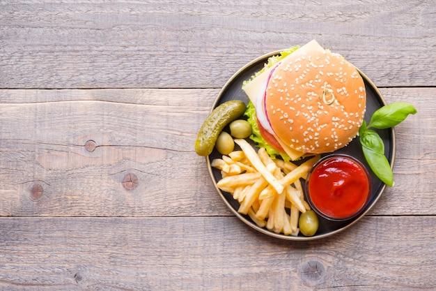 Vista superior de hambúrgueres com molho e batatas fritas na madeira