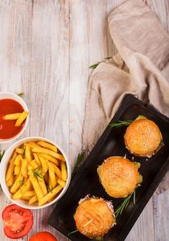 Vista superior de hambúrgueres de carne com batatas fritas e molho