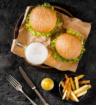 Vista superior de hambúrgueres e batatas fritas com cerveja