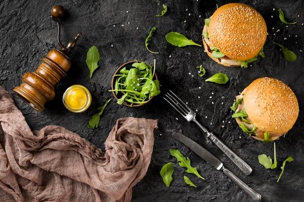 Vista superior de hambúrgueres no balcão com talheres