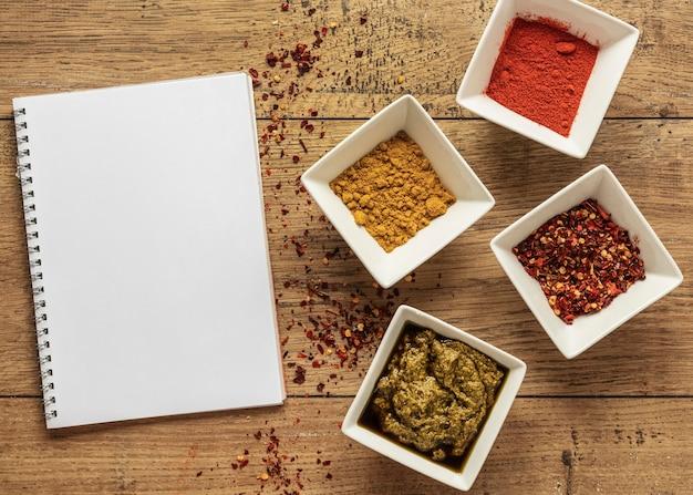 Vista superior de ingredientes alimentares com caderno e especiarias