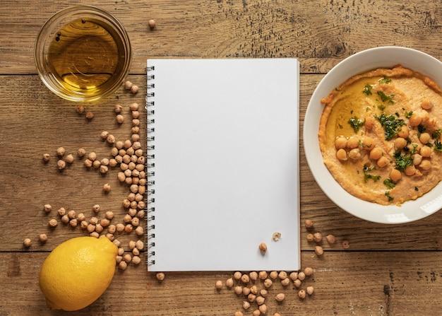 Vista superior de ingredientes alimentares com caderno e grão de bico