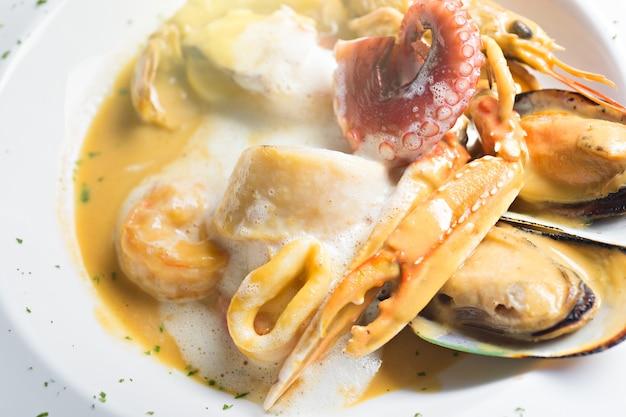 Vista superior de ingredientes de alimentos de fusão com porcaria, mexilhões, camarão e lula vermelha pored com whi