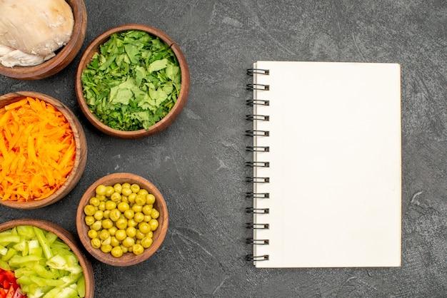 Vista superior de ingredientes de salada com frango e verduras na mesa escura salada de alimentos dietéticos