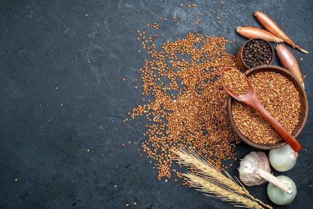 Vista superior de ingredientes frescos de trigo sarraceno em um prato marrom em um espaço cinza escuro