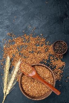 Vista superior de ingredientes frescos de trigo sarraceno em um prato marrom no espaço cinza