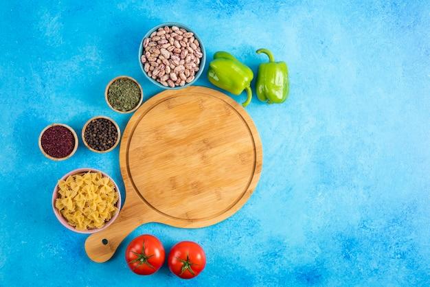 Vista superior de ingredientes frescos e saudáveis. feijão cru e macarrão com legumes sobre fundo azul.
