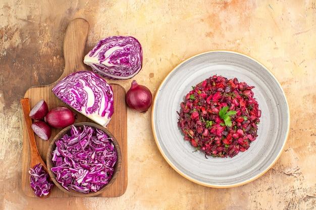 Vista superior de ingredientes frescos em uma tábua de madeira junto com a deliciosa salada em um prato de cerâmica juntos em um fundo de madeira com espaço para texto