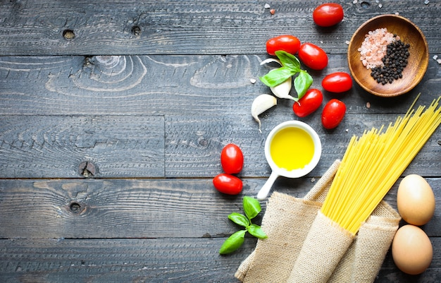 Vista superior de ingredientes italianos para tomate e espaguete basílico.