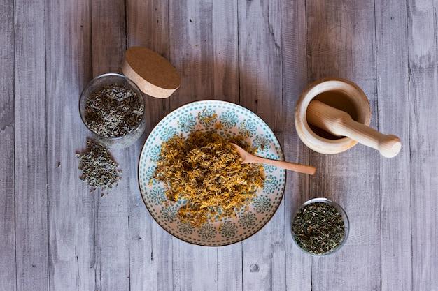 Vista superior de ingredientes saudáveis na mesa, pilão de madeira, açafrão amarelo, lavanda e folhas naturais verdes. de perto, durante o dia