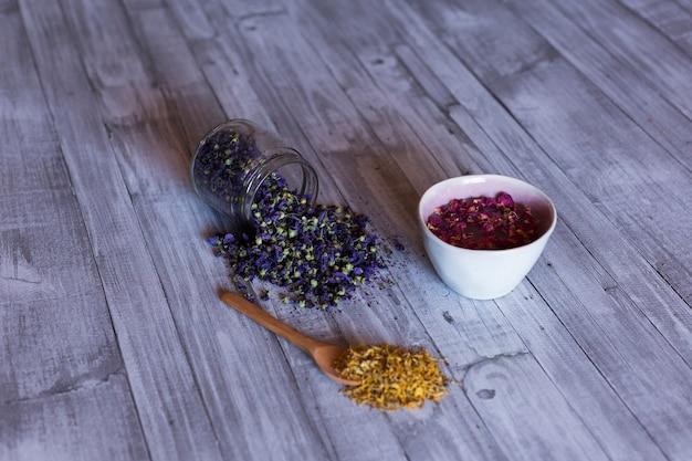 Vista superior de ingredientes saudáveis na mesa, rosas em uma tigela, açafrão amarelo e folhas naturais de lavanda. de perto, durante o dia