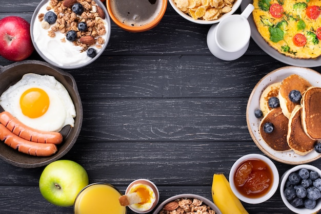 Vista superior de iogurte e cereais com ovo e salsichas no café da manhã