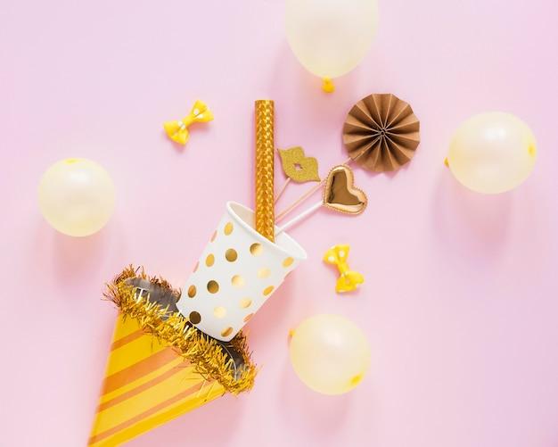 Vista superior de itens de festa em fundo rosa