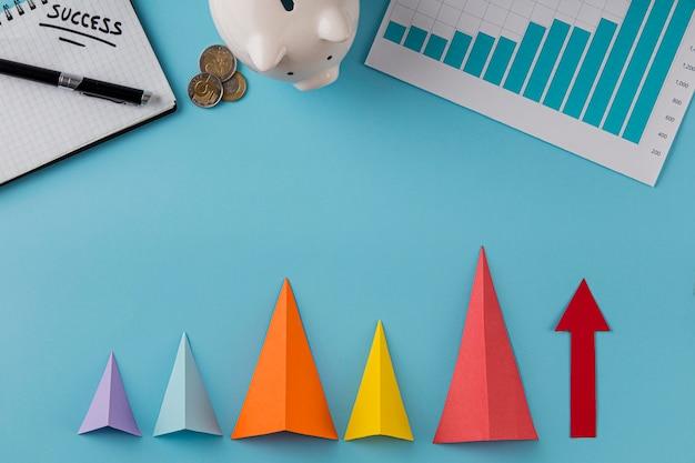 Vista superior de itens de negócios com cofrinho e cones de crescimento