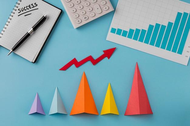 Vista superior de itens de negócios com cones de crescimento e flecha