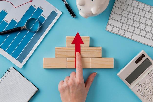 Vista superior de itens de negócios com gráfico de crescimento e mão na seta apontando para cima
