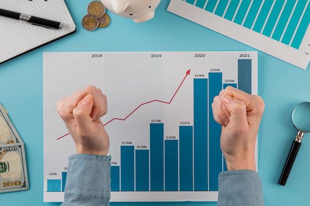 Vista superior de itens de negócios com gráfico de crescimento e mãos em punhos