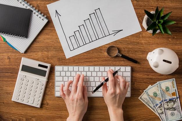 Vista superior de itens de negócios com gráfico de crescimento e mãos usando o teclado