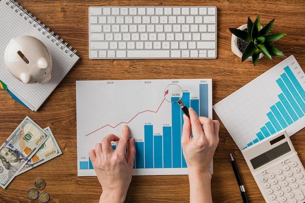 Vista superior de itens de negócios e gráfico de crescimento com a mão segurando uma lupa