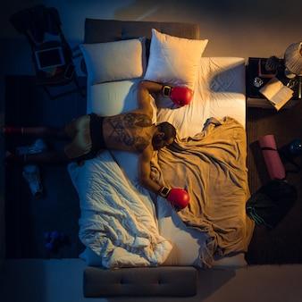 Vista superior de jovem boxeador profissional, lutador dormindo em seu quarto com roupas esportivas e luvas