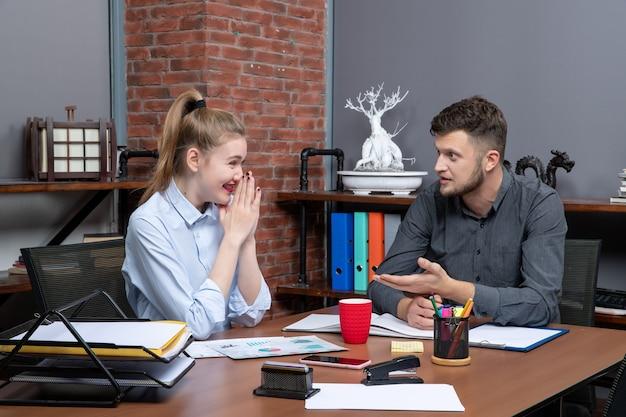 Vista superior de jovens colegas de trabalho que trabalham duro discutindo um problema com expressão facial de surpresa em ambiente de escritório