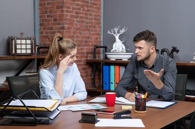 Vista superior de jovens colegas de trabalho que trabalham duro discutindo uma questão importante no ambiente de escritório