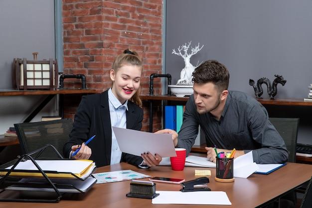 Vista superior de jovens funcionários de escritório ocupados discutindo uma questão importante do documento no escritório