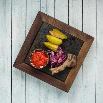 Vista superior de kebab de costela de cordeiro com batatas fritas, servido com molho de tomate