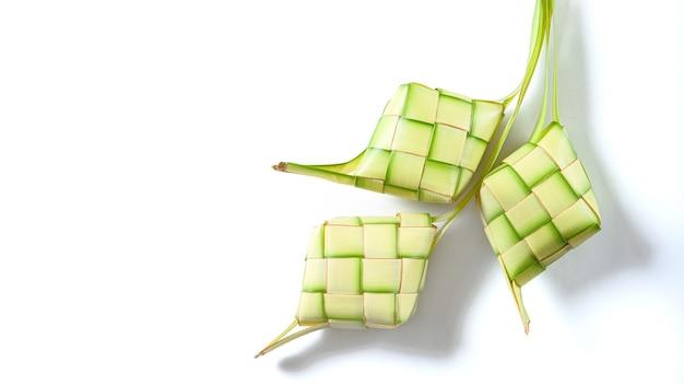 Vista superior de ketupat isolada no fundo branco. prato típico feito de arroz envolto em invólucros feitos de folhas jovens de coco trançadas.