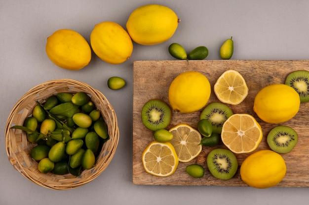 Vista superior de kinkans levemente doces em um balde com limões e kiwi isolados em uma placa de cozinha de madeira em uma parede cinza