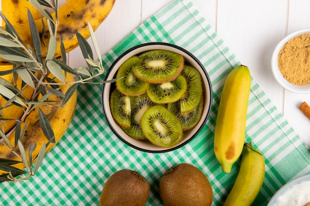 Vista superior de kiwi fatiado em uma tigela, frutas frescas de banana em madeira branca