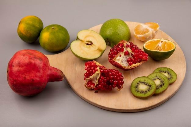 Vista superior de kiwi fatiado saudável com tangerina de maçã e romã em uma placa de cozinha de madeira