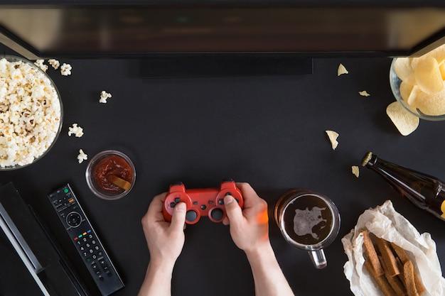 Vista superior de lanches e alimentos pouco saudáveis com o laptop em fundo preto, conceito de jogador