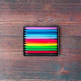 Vista superior de lápis de cera coloridos na mesa de madeira